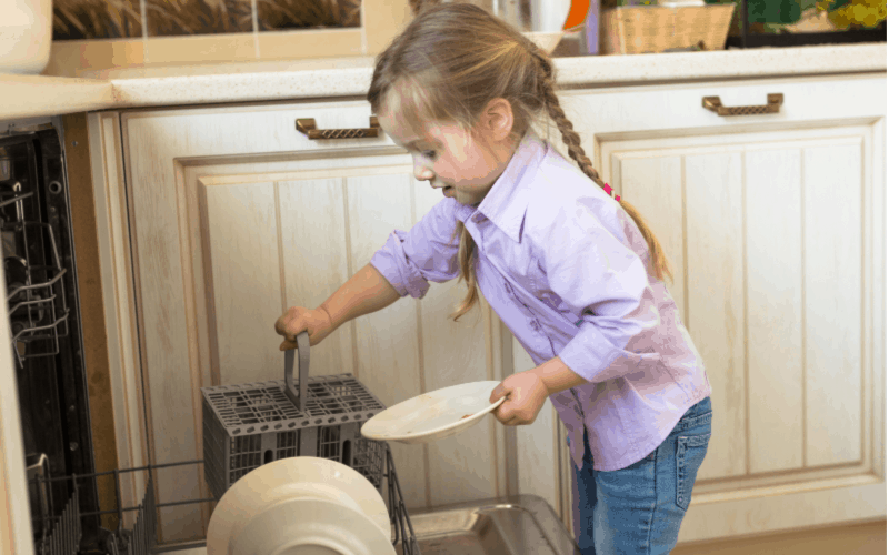 Responsible child loading dishwasher
