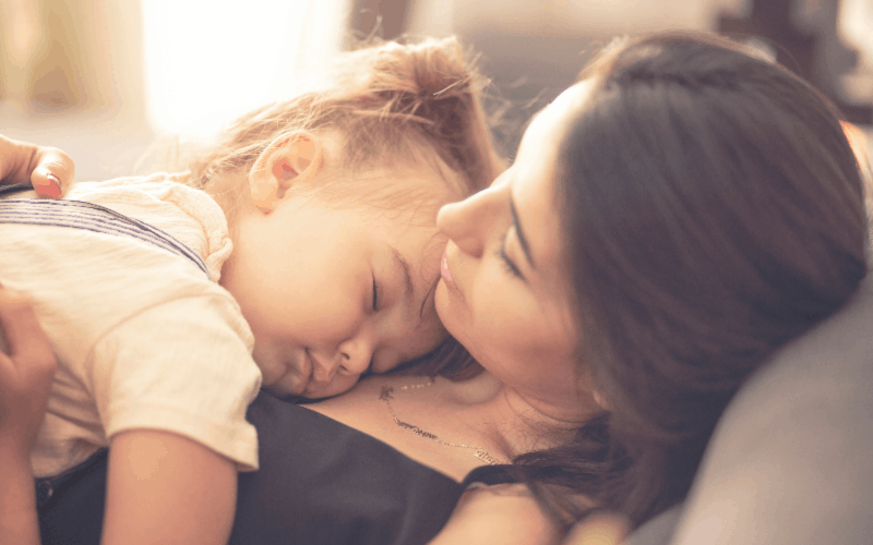 Mother holding sleeping daughter - rewards of parenting