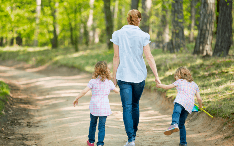 Mother taking walk with children: rewarding parenting moments